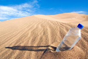 cold-bottle-of-water-sitting-in-sand-duneshutterstock_13378444-custom